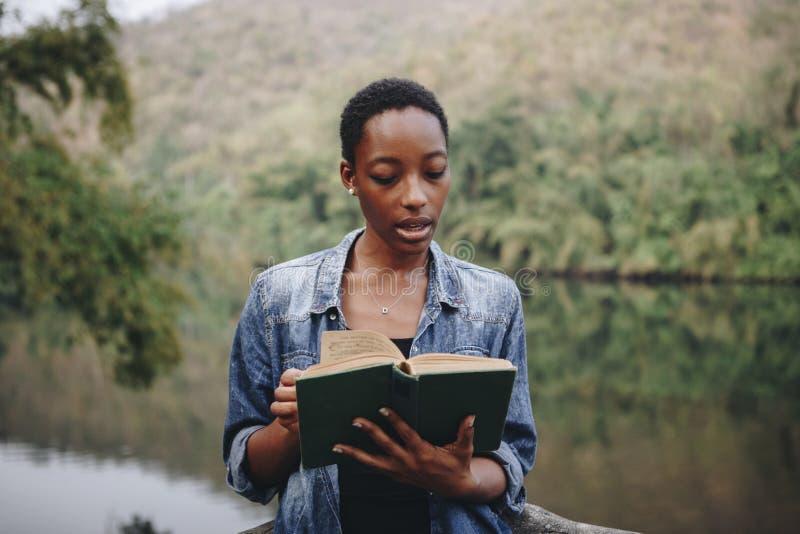 读售票的妇女在森林里 库存照片