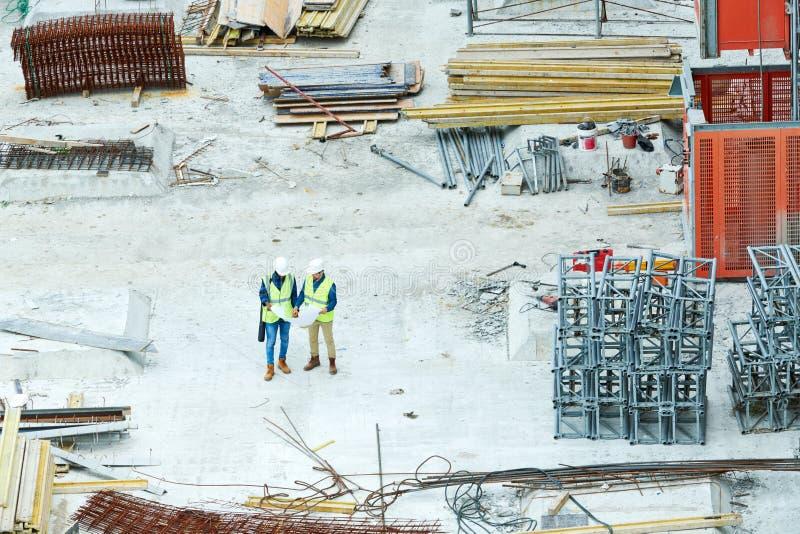 读图纸的房屋检查员在建造场所 免版税库存照片