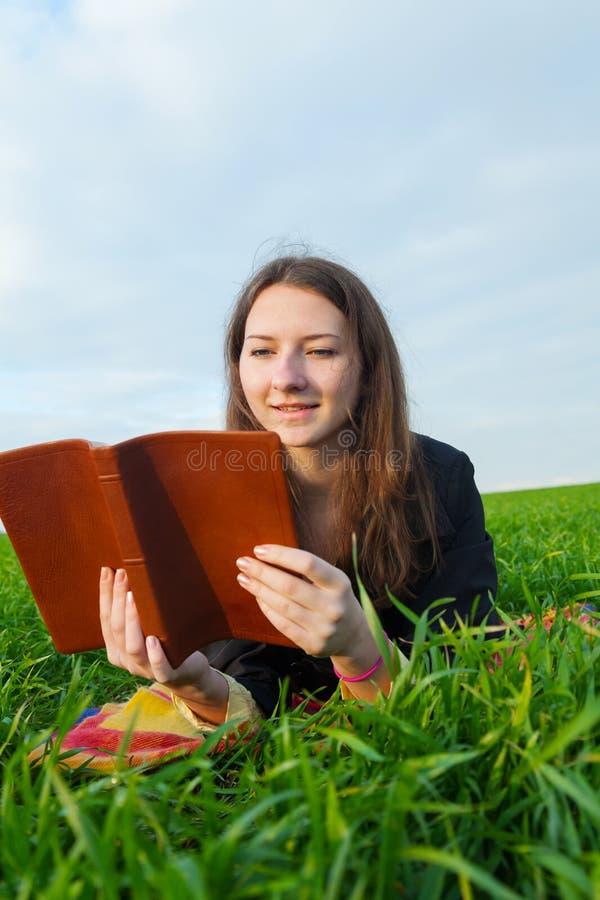 读圣经的青少年的女孩户外 图库摄影