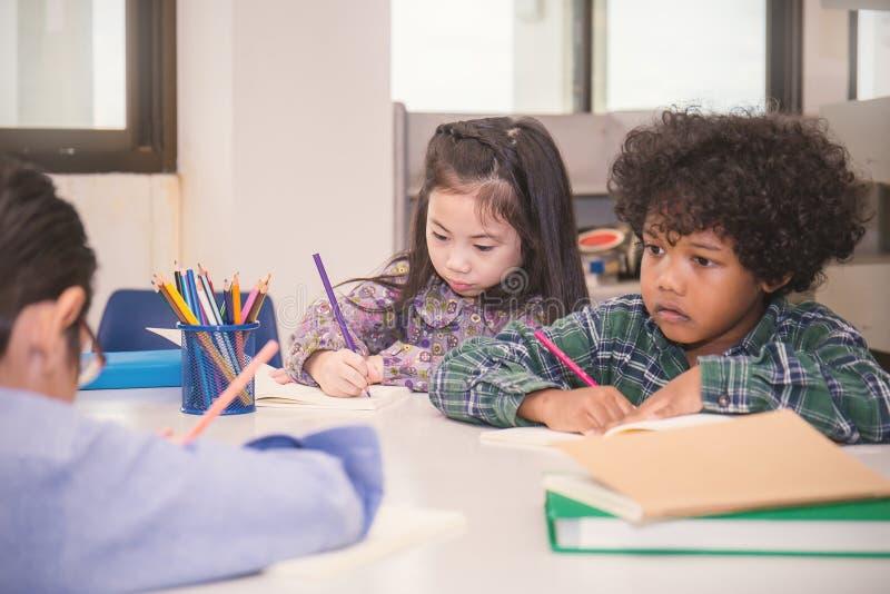 读在一把椅子的四个孩子在教室 免版税库存照片