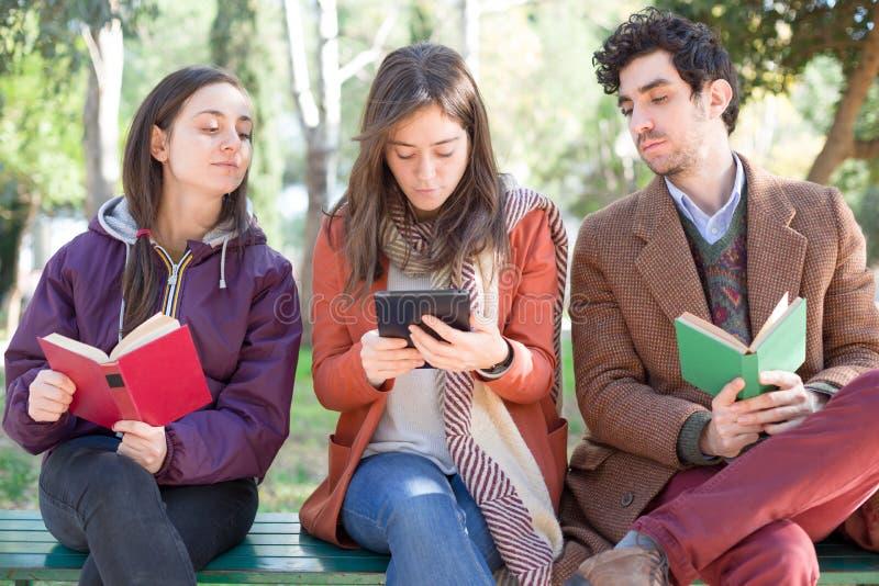 读在公园的三个人 免版税库存照片