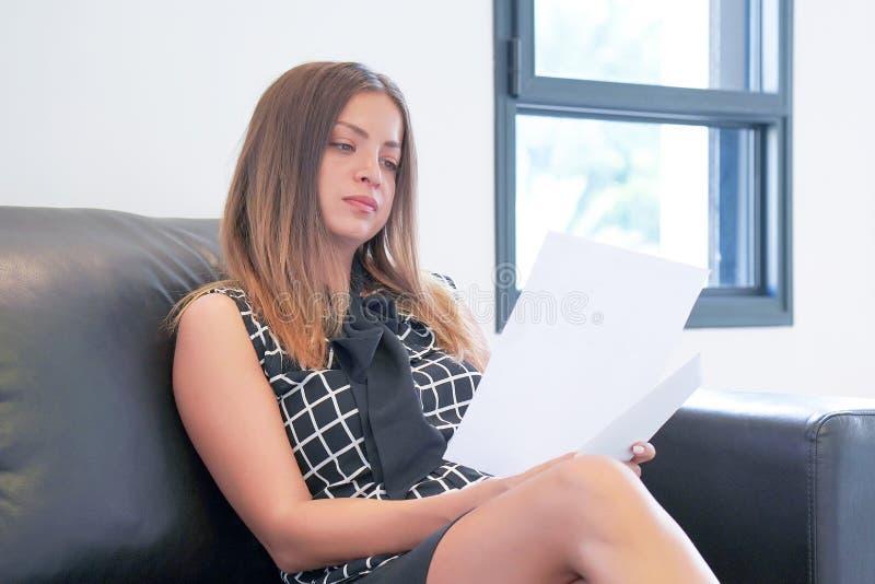 读在办公室工作区的女商人一个文件 库存图片