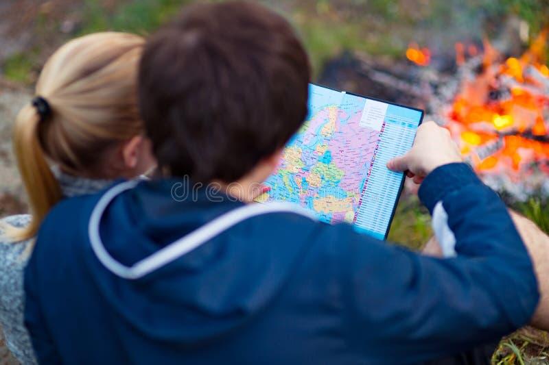 读地图的两三个游人远足者 男人和妇女坐 库存图片