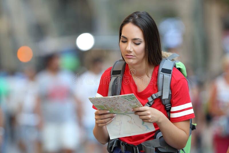 读地图的Frustated青少年的游人 免版税图库摄影