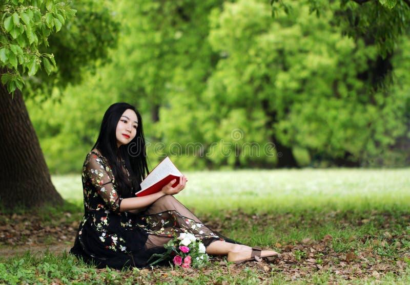 读坐在开花树下的一本书 免版税库存图片