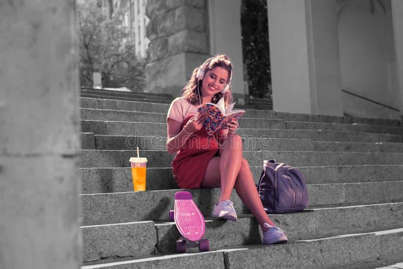 读她喜爱的时尚坐的外部的美丽的艺术系学生 库存图片