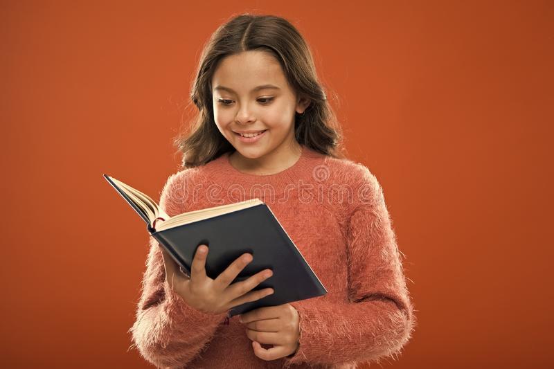 读孩子的活动 女孩举行书读了在橙色背景的故事 孩子享用看书 ?? 免版税库存图片