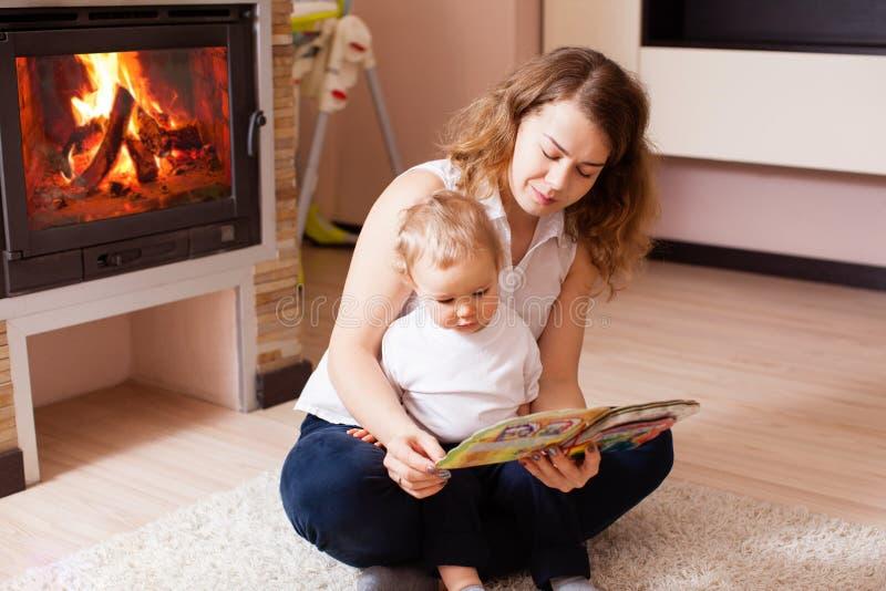 读对她的儿子的年轻母亲在地板 免版税库存图片