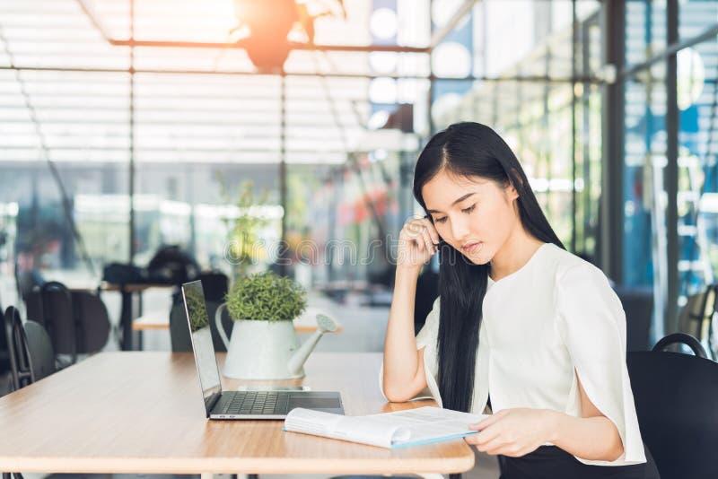读报告的年轻女商人她的拿着笔的手坐在咖啡店 免版税库存照片