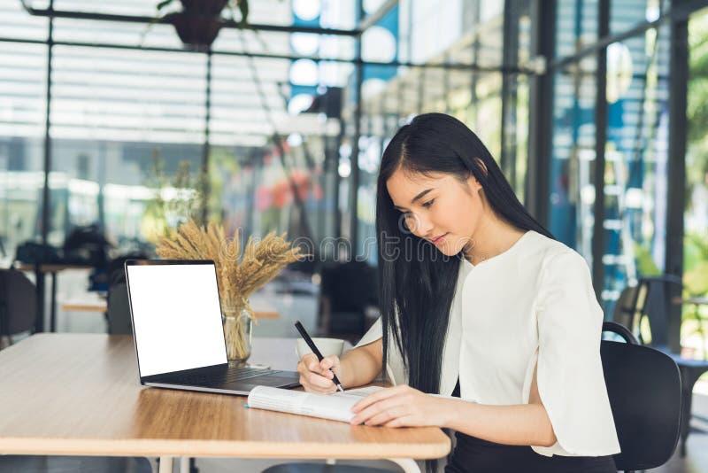 读报告的年轻女商人她的拿着笔的手坐在咖啡店 库存照片