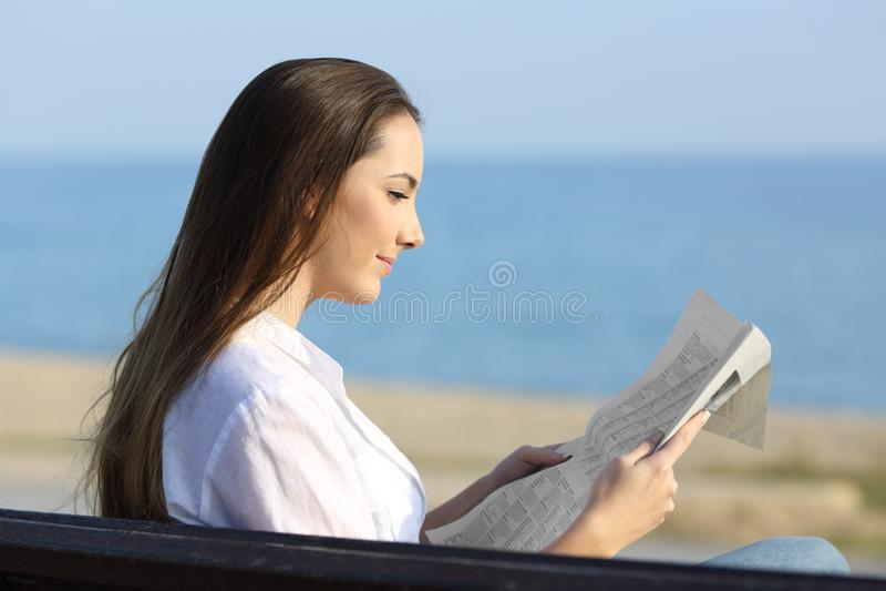 读报纸的妇女外面在海滩 免版税图库摄影