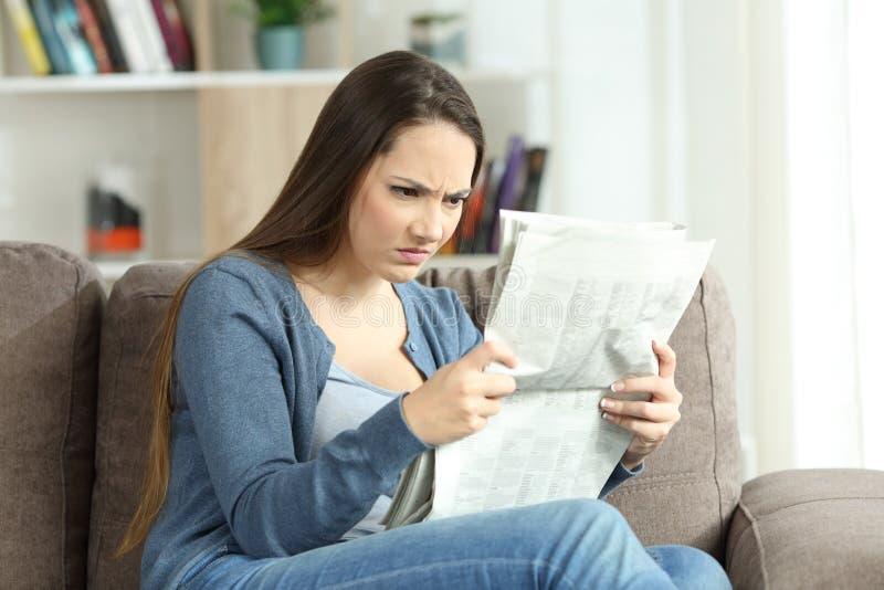 读报纸的恼怒的妇女在长沙发 免版税库存图片