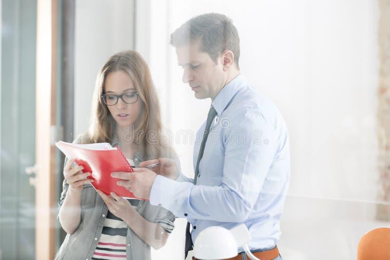 读文件的严肃的企业同事在办公室 免版税库存图片