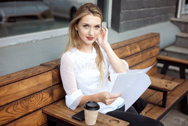 读文件的妇女,当坐在咖啡馆,享用一杯早晨咖啡,她的手时特写镜头视图  免版税库存图片