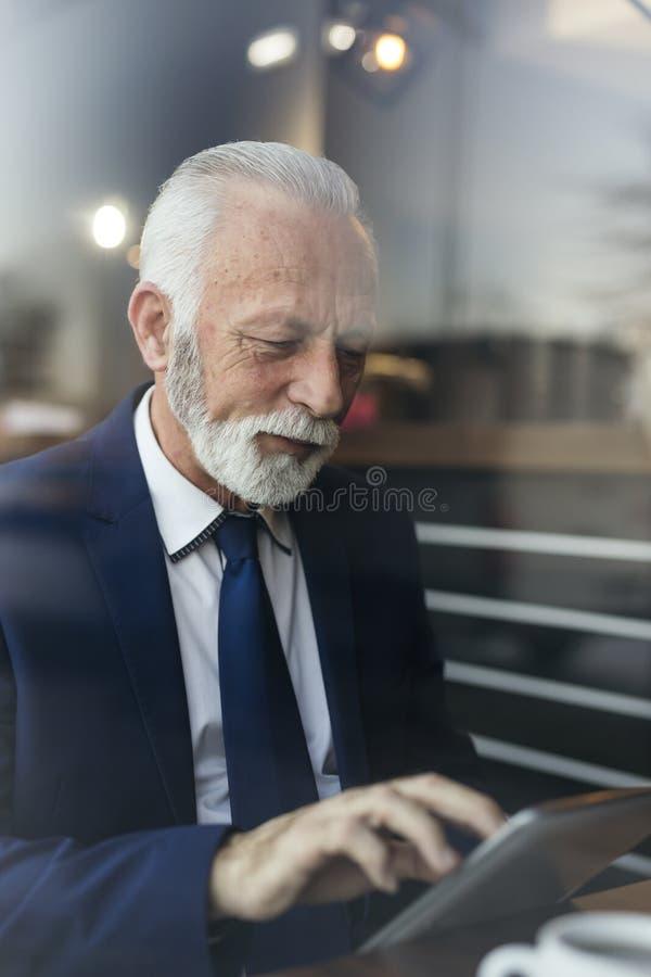 读新闻的资深商人在片剂计算机 免版税库存照片