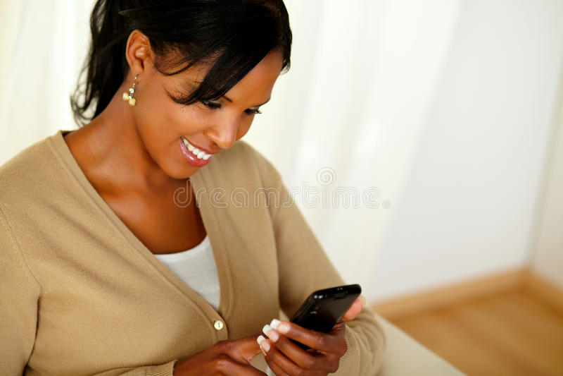 读消息的迷人的成人女孩在移动电话 免版税库存照片