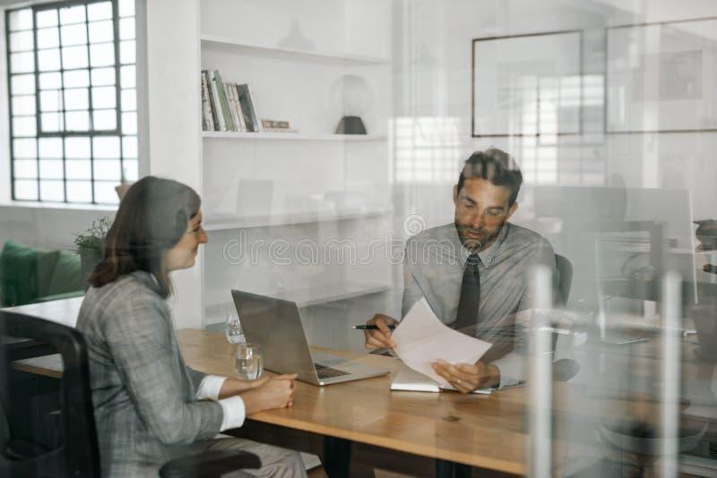 读申请人的简历的微笑的经理在采访中 免版税库存照片