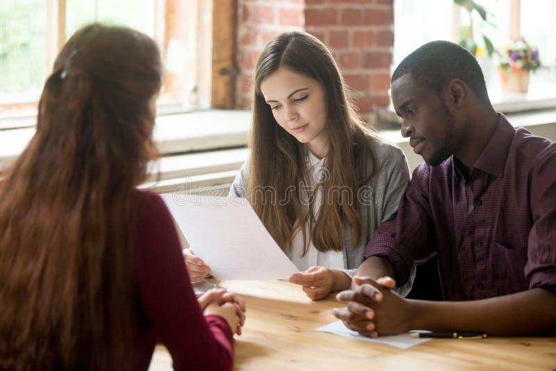 读申请人简历的多种族经理在聘用期间 免版税库存图片