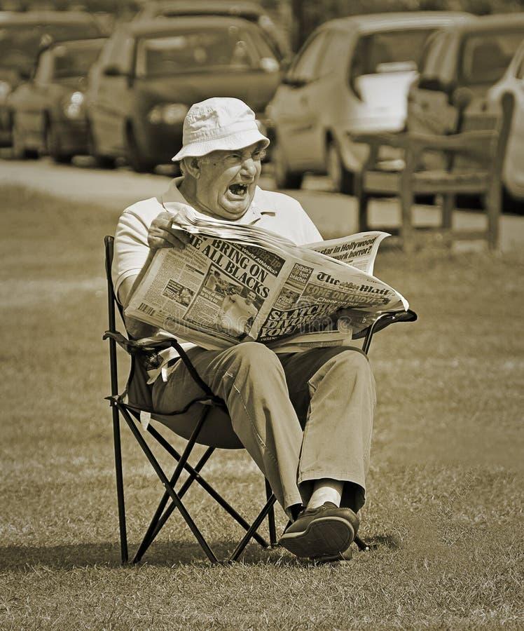 读的乏味的星期日早晨报纸 免版税库存照片