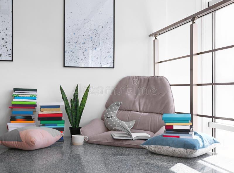 读的舒适地方与书和扶手椅子坐垫 免版税库存图片