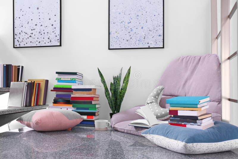 读的舒适地方与书和扶手椅子坐垫 图库摄影