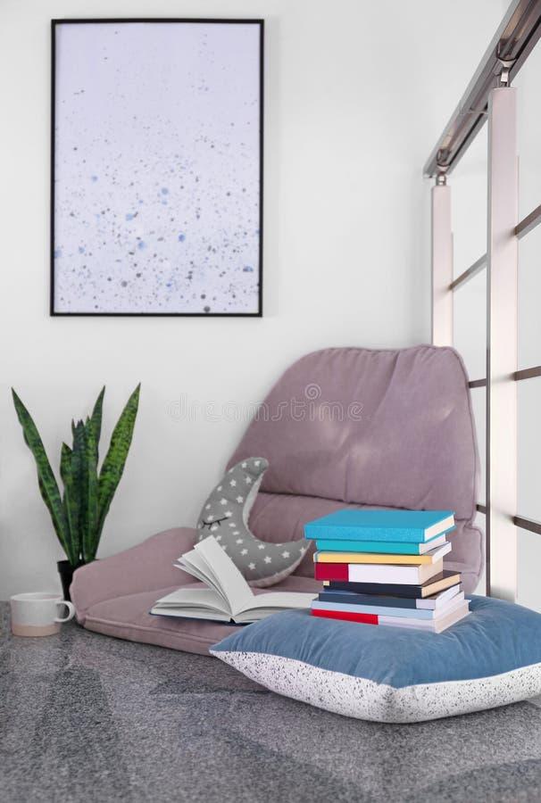 读的舒适地方与书和扶手椅子坐垫 库存图片