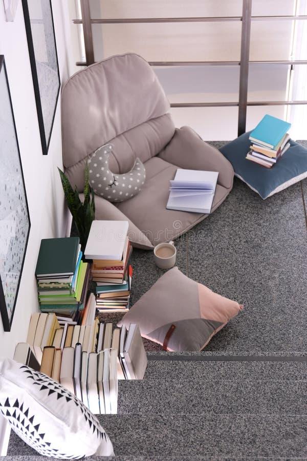 读的舒适地方与书和扶手椅子坐垫 库存照片