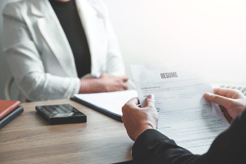 读简历的高级管理人员妇女在面试雇员年轻人会议申请人和补充期间 免版税图库摄影
