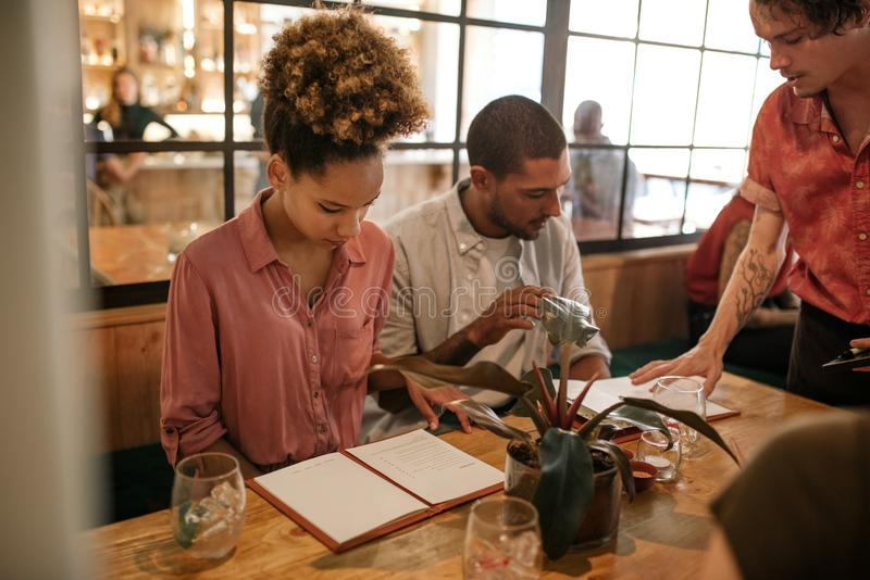 读菜单的小组年轻朋友在餐馆桌上 免版税图库摄影
