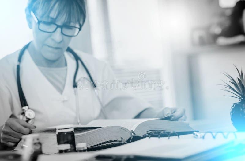 读课本的女性医生;光线影响 库存照片