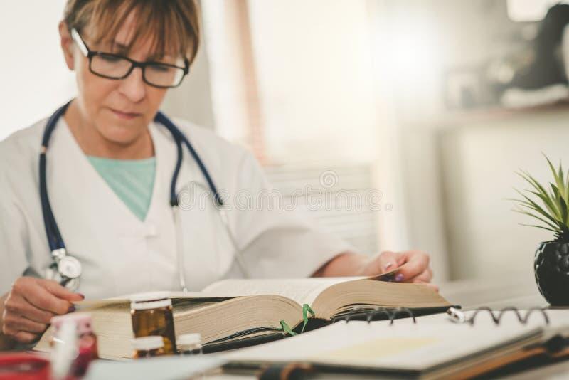 读课本的女性医生 图库摄影