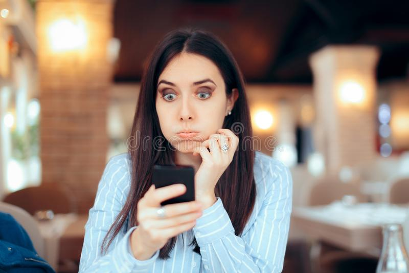 读迫切SMS文本的担心的女孩在智能手机 免版税图库摄影