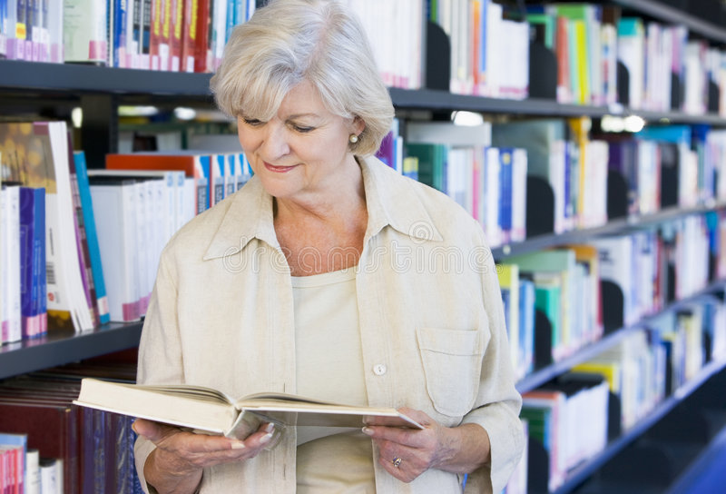 读高级妇女的图书馆 免版税库存图片