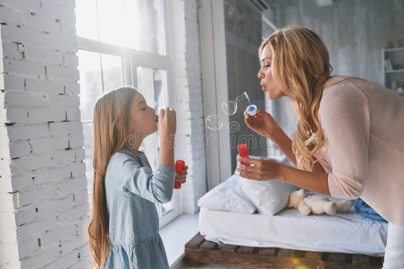 谁变得更大?母亲和女儿吹的肥皂泡,当s时 免版税库存图片