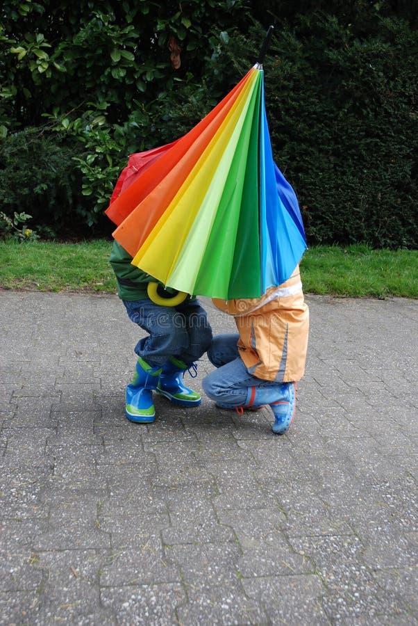 谁在伞、男孩或者女孩下? 库存照片