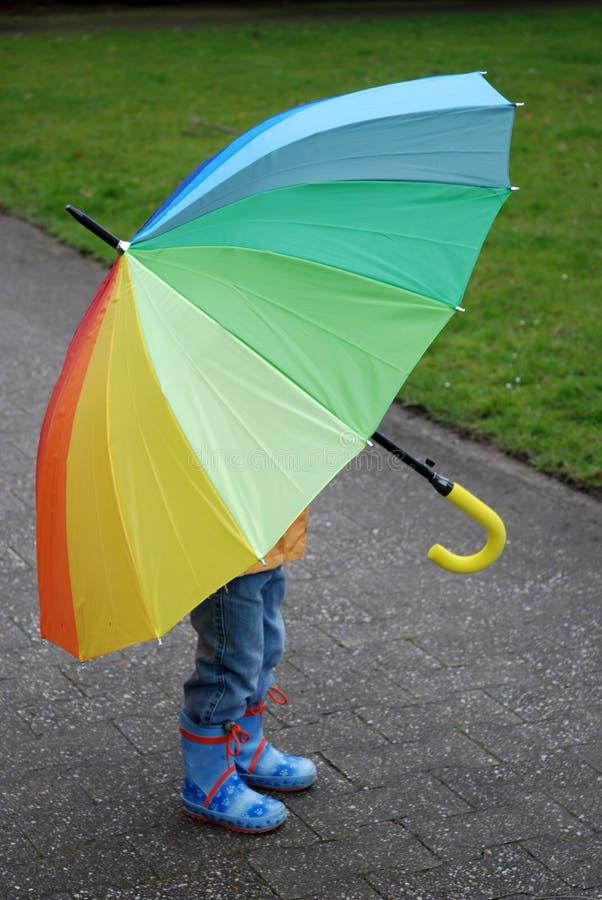 谁在伞、男孩或者女孩下? 图库摄影
