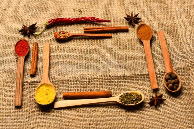 调味品和香料概念 匙子用作为红辣椒、姜黄和桂香的香料在麻袋布背景 免版税库存图片