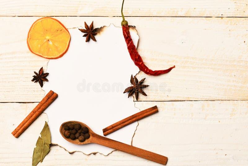 调味品的构成在纸片断的 木匙子用胡椒 库存图片