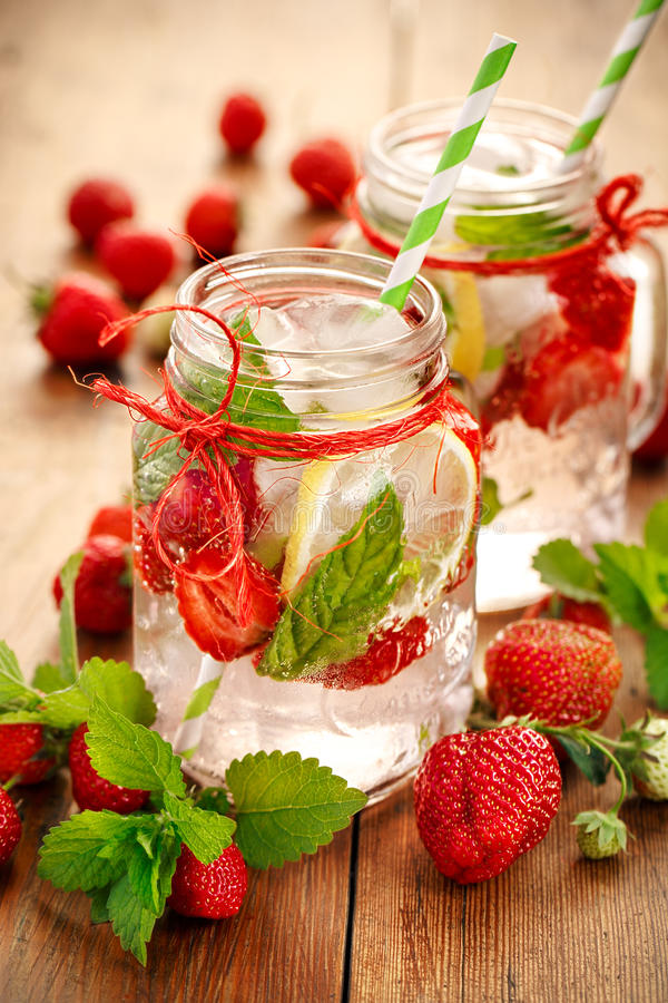 调味的水用新鲜的草莓、柠檬和薄菏 图库摄影