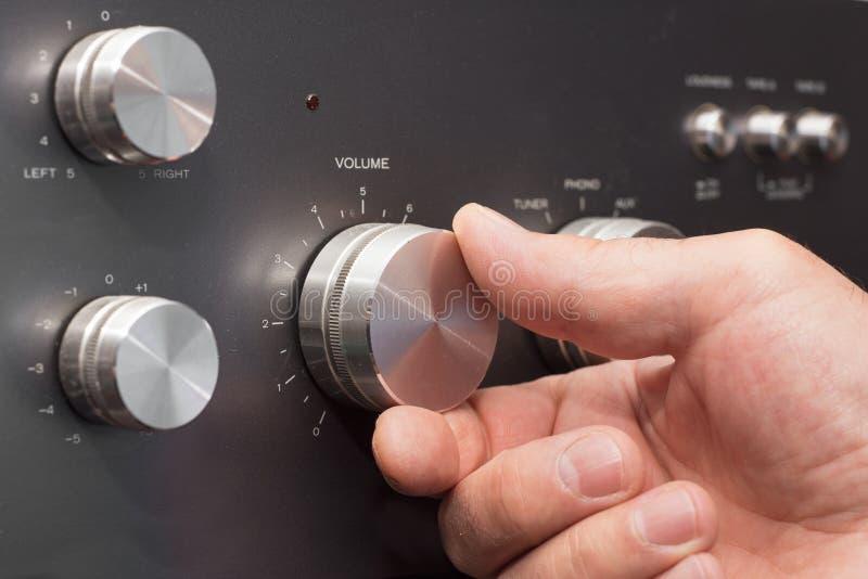 调大在立体音响的容量的手 免版税库存图片
