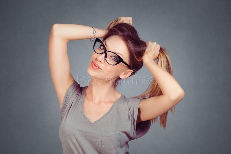 调情的人 看照相机的美丽的性感的妇女女孩举行对挥动的头发 免版税图库摄影
