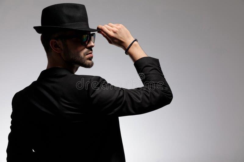 调整他的盖帽的一个神奇偶然人的背面图 免版税库存照片