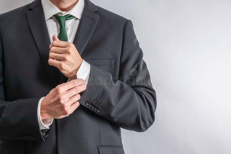 调整他的袖子的穿着体面的商人 库存图片