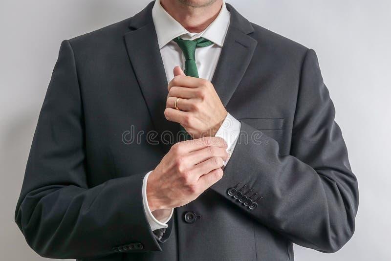 调整他的袖子的穿着体面的商人 免版税图库摄影