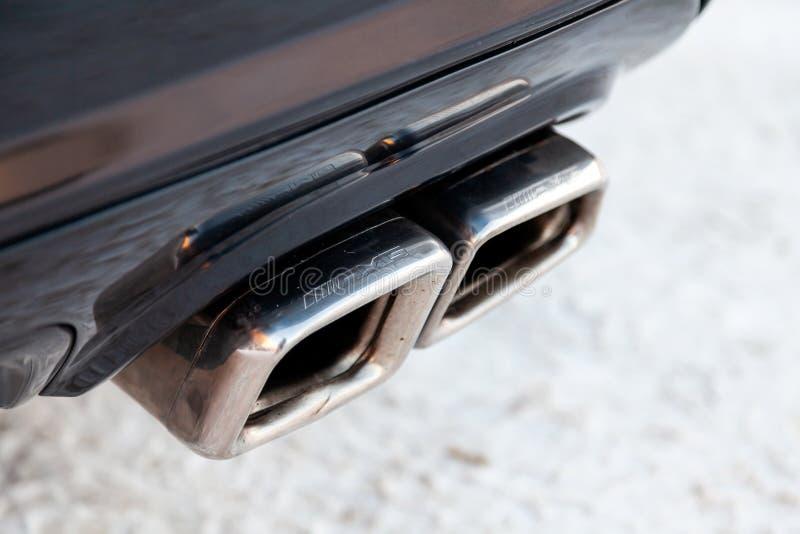 调整围巾和发光的镀铬物镀了一个黑被装备的汽车奔驰AMG模型特写镜头新的强有力的零件的排气管  免版税库存照片