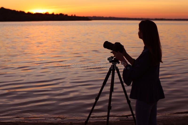 调整在三脚架的年轻女性摄影师专业照相机 库存照片