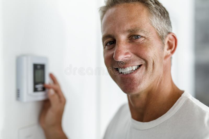 调整在家庭供暖系统的微笑的人温箱 库存图片