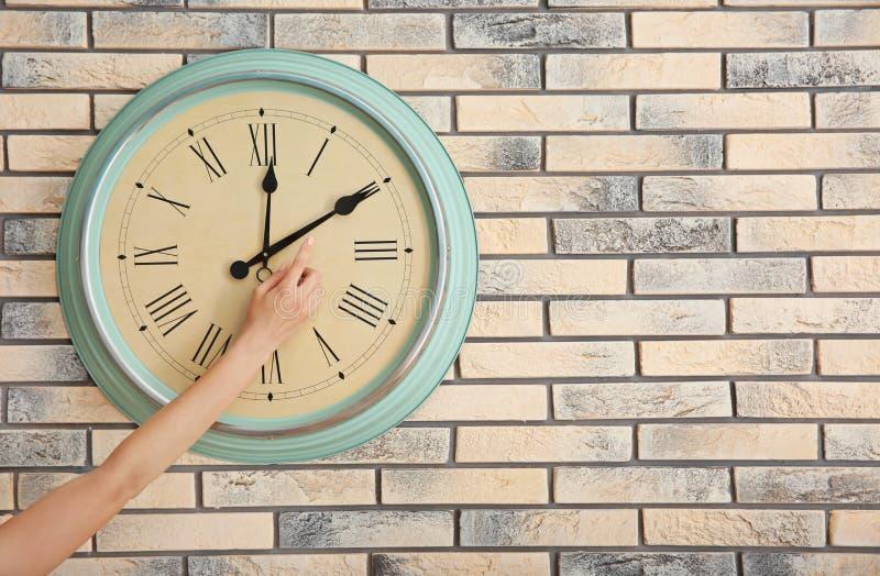 调整在时钟的妇女时间对砖墙 免版税库存照片