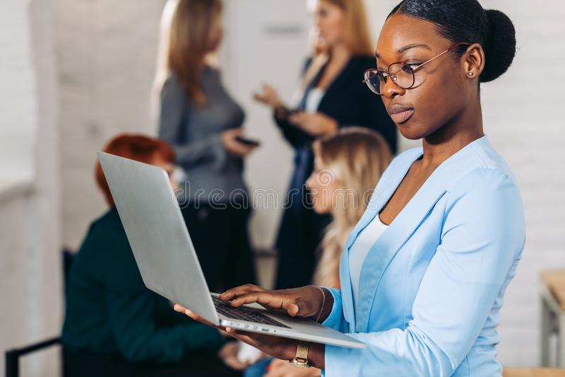 调整她的膝上型计算机的企业黑人妇女,站立与后边同事 免版税库存图片