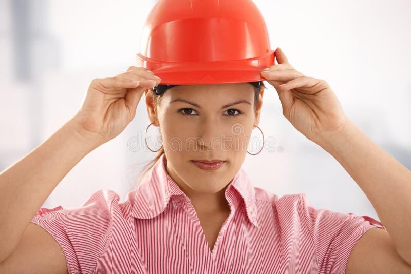 调整建筑师女性安全帽她 免版税库存照片